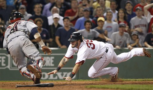 Boston Red Sox's Jarrod Saltalamacchia dives for home plate to score the winning run as Cleveland Indians catcher Carlos Santana tries to tag him in the ninth inning Tuesday at Fenway Park in Boston. The Red Sox won 3-2.
