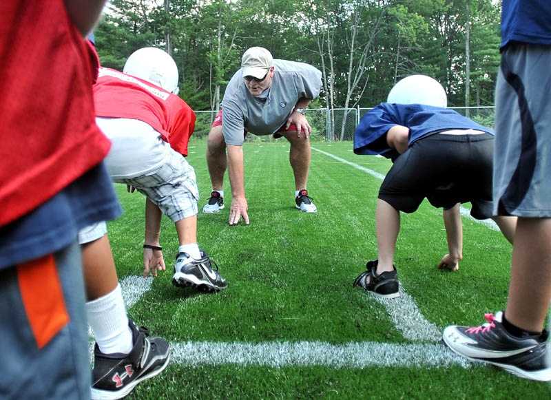 Former New York Jets defensive lineman Marty Lyons works with a group of local football players at Camp Tracy in Oakland Friday.