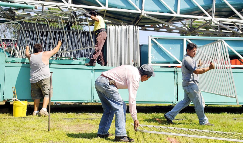 Workers assemble a Rockwell Amusements ride Monday on the fairway at the Monmouth Fairgrounds. The Cochnewagan Agricultural Society's annual festival commences Wednesday and concludes Saturday.