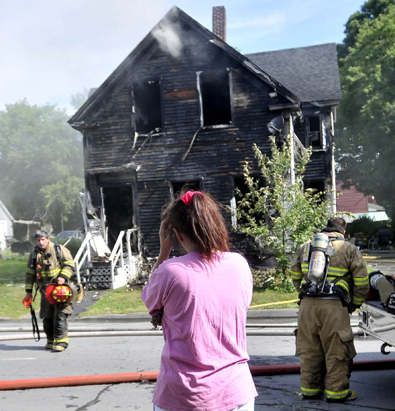 Tracey Bragdon stands in front of her Oak Street home in Waterville on Tuesday as firefighters battle the blaze.