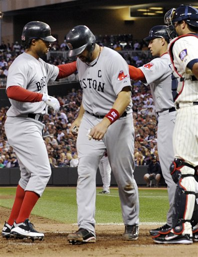 Boston's Darnell McDonald, left, high fives on-deck batter Jacob Ellsbury, second from right, after driving in Jason Varitek, center, with a two-run home run off Minnesota's Francisco Liriano in the fifth inning Tuesday in Minneapolis. At right is Twins catcher Drew Butera.
