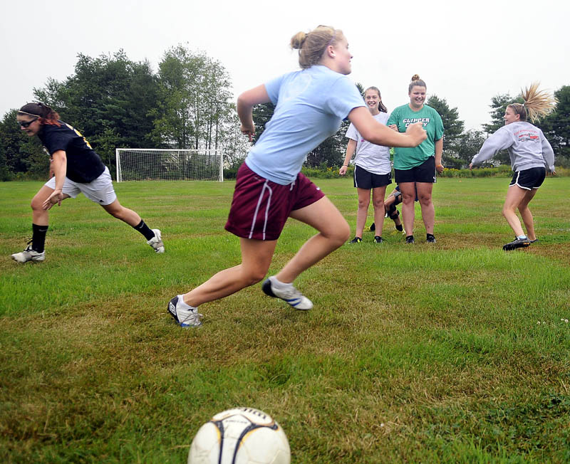 TEAM BUILDING: Richmond High School girls soccer players chase each other across the field Monday during the defending Class D champions first day of practice. Athletes at schools across Maine took to soggy fields for the commencement of the 2011-2012 high school sports season.