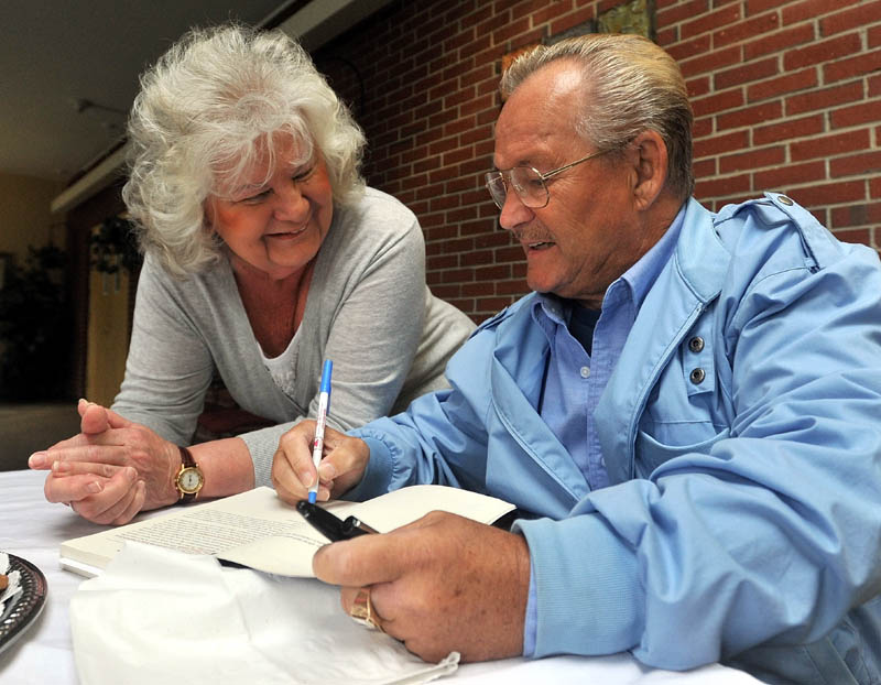 FOR YOU: Ron Turcotte signs an autograph for Carole Hemingway before speaking at Spectrum Generations at the Muskie Center on Tuesday in Waterville. Turcotte is a Hall of Fame jockey and is most famously known for riding Secretariat to the Triple Crown in 1973.