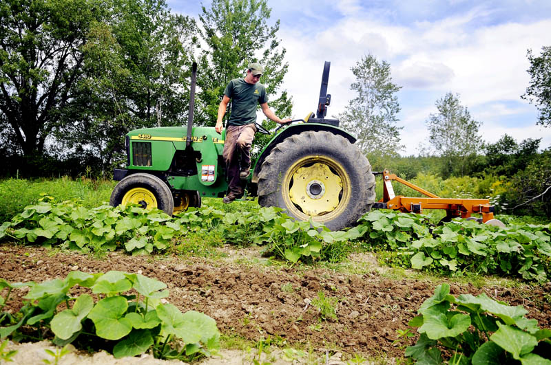 CHANGE IN PLAN: Steve Christianson dismounts a tractor after harrowing a summer squash patch Tuesday in Mount Vernon. The manager of Belle Vue Farm, in Readfield, was relieved to learn that the federal government Wednesday scrapped plans to require farmers to get commercial drivers licenses to operate their tractors.