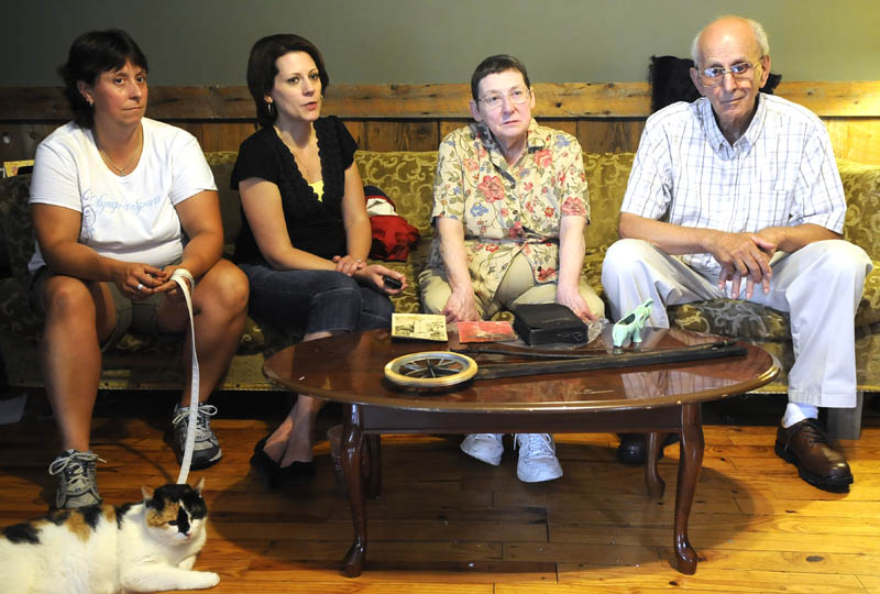 SURVIVORS: Harold and Marlene, second from right, Webber lost their Mount Vernon home to a fire last week. The home is where they raised their daughters, Emily Webber, left, and Joyce Jones. A lightning strike destroyed the old schoolhouse that the Webbers have occupied since 1969. Neighbors and friends have helped them find and save items from the home.