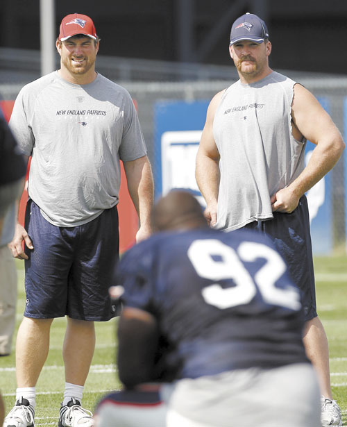BACK FOR MORE: Signed but unable to practice yet, New England Patriots offensive lineman Matt Light, left, and Logan Mankins check out new teammate Albert Haynesworth (92) during training camp Tuesday in Foxborough, Mass.