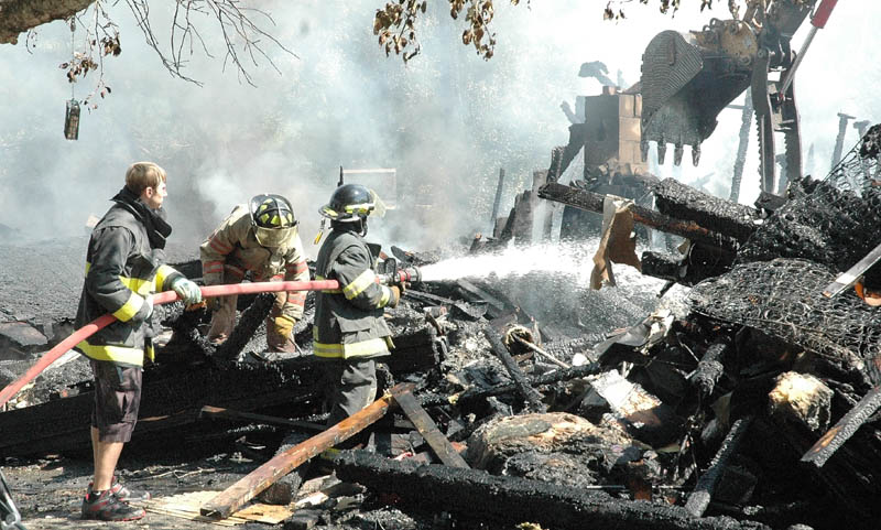 Members of the Athens Volunteer Fire Department soak what's left of the home of Dwayne and Mary Brown on Valley Road in West Athens on Thursday morning. The family of five lost three dogs and all their belongings. They were not insured.