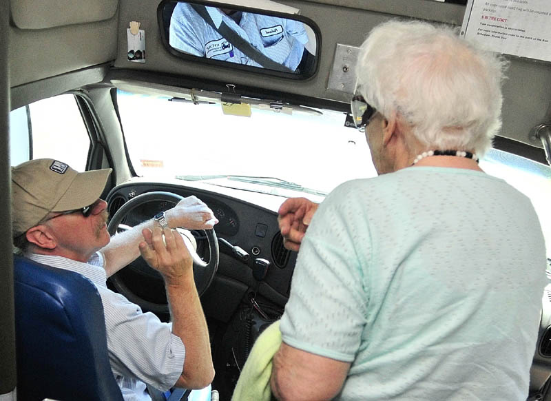 As she gets off the bus, passenger Fay Scholz, of Hallowell, confers with driver Roland St. Pierre, left, about how she can get another Kennebec Explorer bus back home after her doctor's appointment in Augusta.