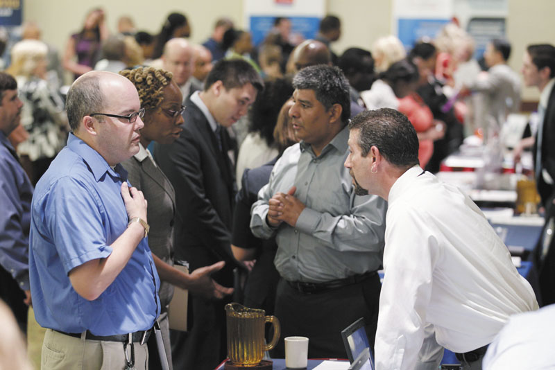 Jjob seeker Manfred A. Lynch, left, speaks Thursday with a recruiter at a job fair in Arlington, Va. The Labor Department announced Friday that hiring picked up slightly in July and the unemployment rate dipped to 9.1 percent as employers added 117,000 jobs.