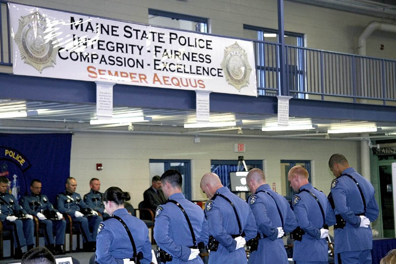 New state troopers bow their heads during the benediction at their ceremony Friday afternoon at the Maine State Criminal Justice Academy in Vassalborough.