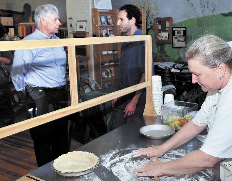 U.S. Rep. Mike Michaud, D-2nd District, left, speaks with Barrels Community Market manager David Gulak as employee Deb Wrobel prepares lunch dishes during a stop in Waterville on Wednesday.