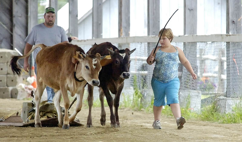 Dionica Robinson walks beside Ace and Edgar as she competes in the farmers pull on Thursday morning at the Monmouth Fairgrounds on Academy Road in Monmouth. The fair runs through Saturday.