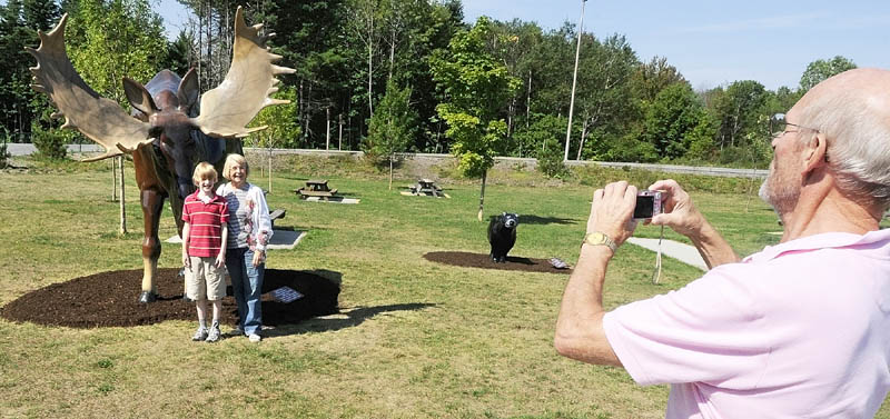 Benjamin Hagle, of Bar Harbor, left, and Nancy Ottman, of St. Paul, Minn., pose in front a fiberglass moose as Jim Hagle, of Nashville, Tenn. snaps their picture on Thursday morning at the West Gardiner Service Plaza on Route 126 that serves both Interstate 95 and the Maine Turnpike.