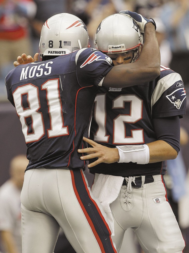 GOODBYE: New England Patriots quarterback Tom Brady (12) hugs wide receiver Randy Moss on Sunday, Sept. 26, 2010. Moss, who caught an NFL-record 23 touchdowns for the Patriots in 2007, will retire, according to his agent.