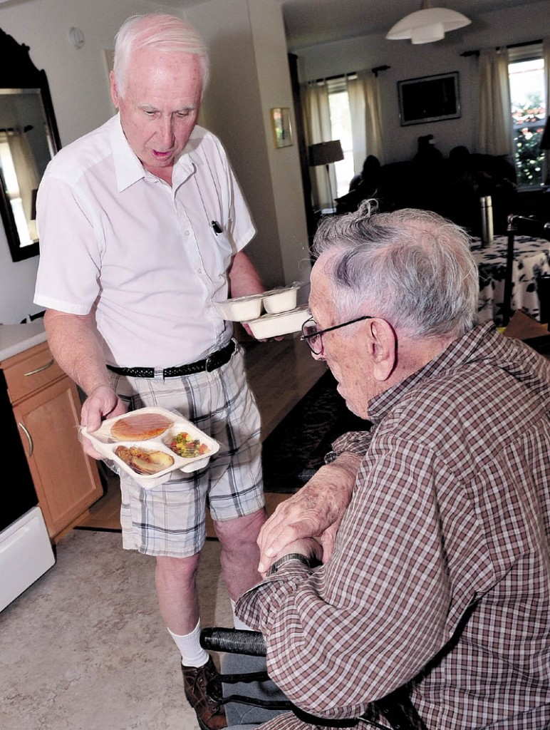 Meals for Wheels driver Gil Pelletier, left, delivers food to Thaddy Gondela in Waterville. Spectrum Generations in central Maine is preparing a new program this fall that incoroprates all fresh, nutritious local foods into its Meals on Wheels and community center dining services for the elderly.