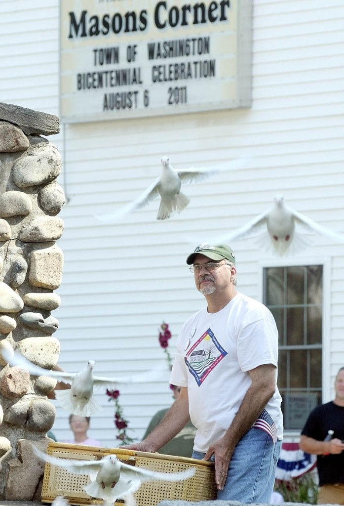 Marc Archambault, of White Doves of Maine, releases a basketful of doves before the parade to celebrate the Town Of Washington's bicentennial on Saturday.