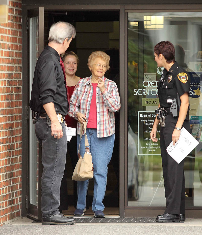 LEAVING UNHARMED: Winslow Police Chief Jeffrey Fenlason and officer Linda Smedberg let customers out of the Winslow Community Federal Credit Union on Monument Street after it was robbed Thursday morning. The robbery occurred around 9:50 a.m.