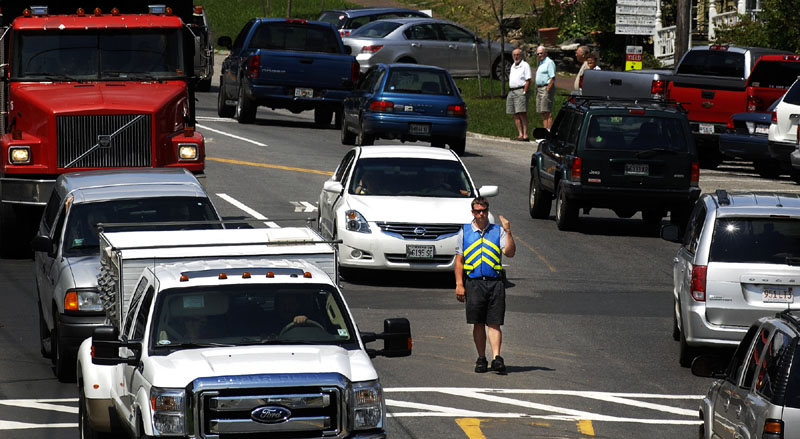 BOTTLENECK: Police officer Alex Greenlaw directs traffic Tuesday through downtown Wiscasset. Greenlaw said he works eight-hour shifts directing traffic in front of Red's Eats on U.S. Route 1 to help pedestrians cross and to try to prevent traffic from backing up.