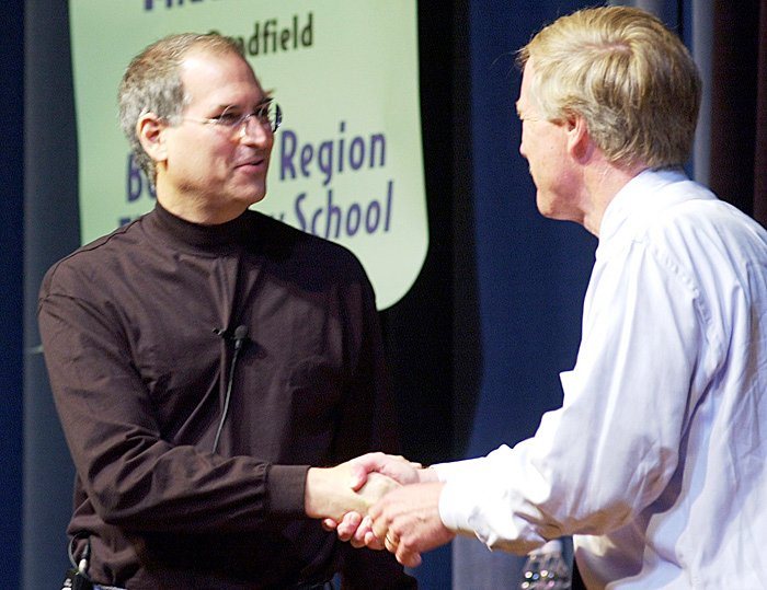 A June 10, 2002, of Steve Jobs, founder and then-president of Apple Computer being greeted by Gov. Angus King as he is introduced at the governor's laptop computer assessment program at Portland High School. Apple iBook laptops were the exclusive laptops bought for the students and Apple provided financial and technical support for the program.