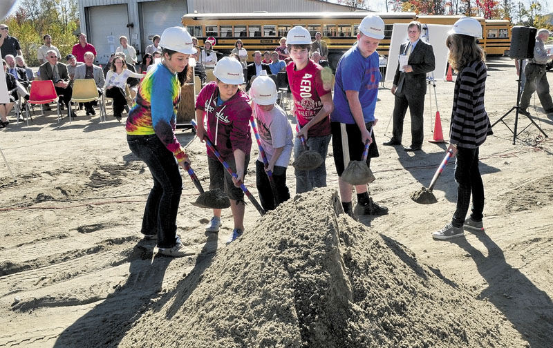 WOOD SPLITTERS: Regional School Unit 18 Superintendent Gary Smith, right, watches as students take part in a groundbreaking ceremony for the Central Biomass Boiler project near the bus garage in Oakland on Tuesday. Students from left are Sydni Collier, Grace Bourgoin, Robert Haldeman, Tristan Friend, Chandler Dugal and Emma Cyr.