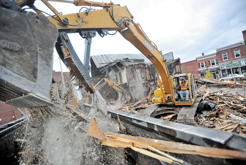 WRECKING CREW: Bruce Obert loads buckets of rubble during the demolition of several vacant buildings in downtown Skowhegan Saturday morning.