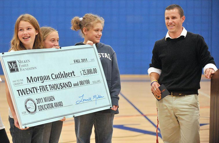 Harrison Middle School students hold a check from the Milken Foundation made out to seventh-grade math and science teacher Morgan Cuthbert in Yarmouth today.