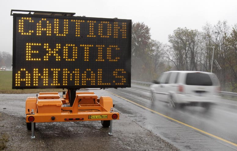 A sign warning motorists that exotic animals are on the loose stands next to I-70 today near Zanesville, Ohio.