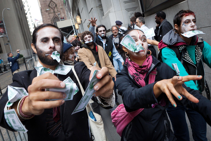 "Protesters from Occupy Wall Street march through New York's financial district dressed as ""corporate zombies"" today."