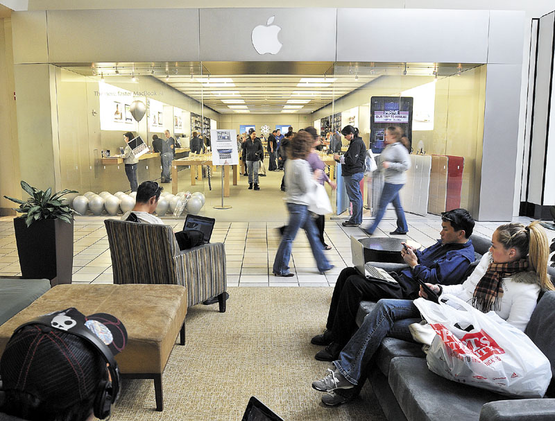 GOING ON WITH BUSINESS: People shop at the Apple Store on Thursday afternoon at the Maine Mall in South Portland. Steve Jobs, co-founder of Apple Inc., died of a rare form of pancreatic cancer Wednesday at age 56.