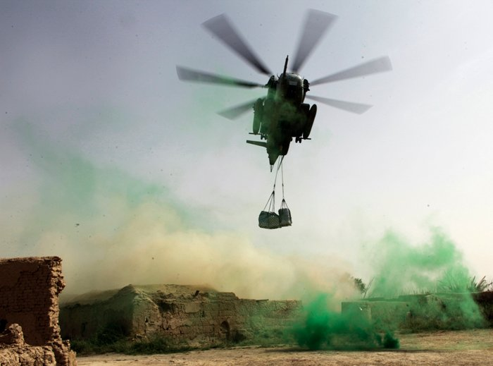 A U.S. military helicopter prepares to drop a pallet of supplies inside a Marine Corps outpost in Helmand province, southern Afghanistan.