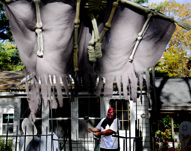 """LET YOUR FREAK FLAG FLY: Donald Hallett hangs a Halloween decoration Tuesday outside his Manchester home. Hallett goes all out setting up his home for the holiday. """"We like to have a little bit of fun,"""" he said."""