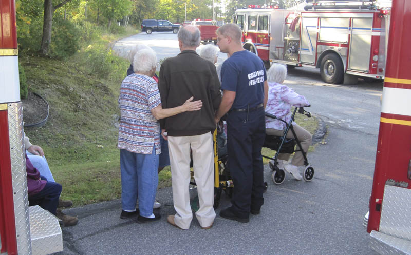 EVACUATION: Gray Birch Apartment complex residents huddle with Gardiner firefighters Monday after several units were evacuated due to a small fire. The blaze was quickly contained and no injuries were reported, according to officials.