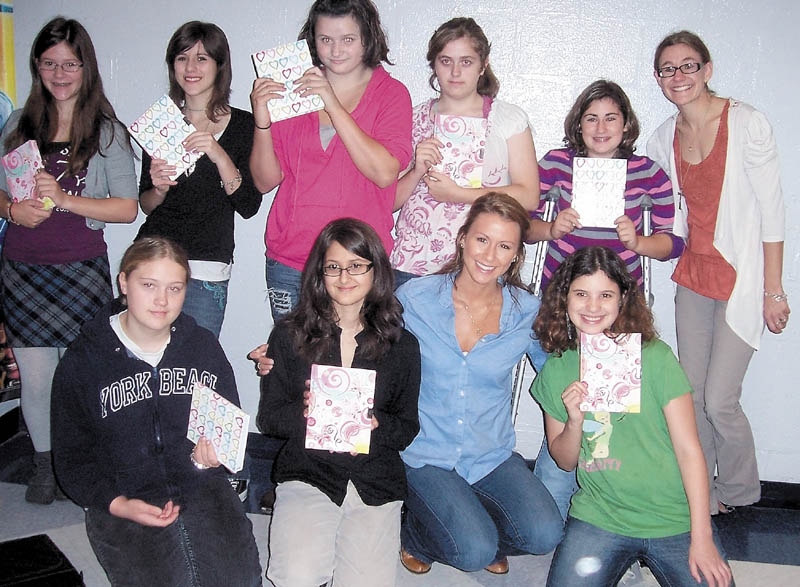 Students at Mt. Blue Middle School in Farmington show off their new journals that Ashley Underwood, 26, of Benton, gave them Tuesday morning. From left in back row are Emily McCarthy, Shamira Tanguay, Destiny Burnell, Miranda Chapman, Jazmine Gorman and art teacher Danielle Guerrette. In front from left are Mikayla Reynolds, Emily Nicholoff, Underwood and Brittany Meryhew.