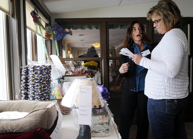 Mary Kay Adams, left, chats Sunday with Kim Nixon while evaluating donated items up for sale at the Kibbles 'N Bids Auction in Manchester. The 13th annual auction, sponsored by Charlies' Super Motor Mall, raised funds for the Kennebec Valley Humane Society.