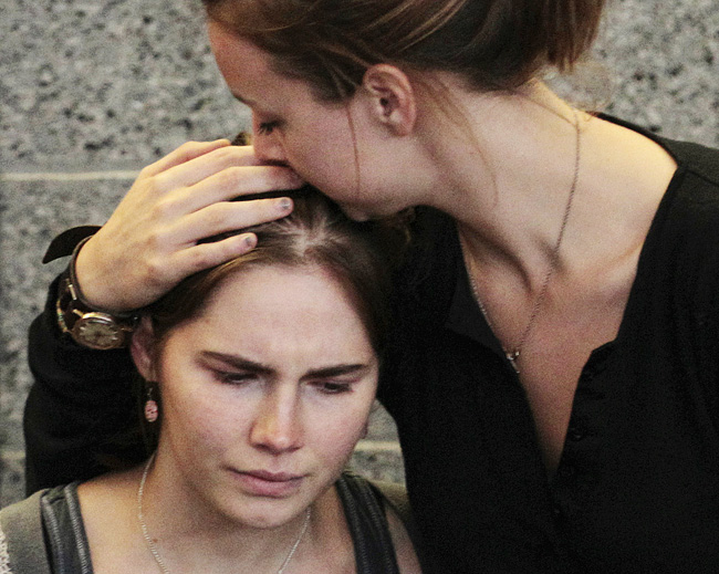 Amanda Knox is comforted by her sister, Deanna Knox, during shortly after her arrival at Seattle-Tacoma International Airport on Tuesday.
