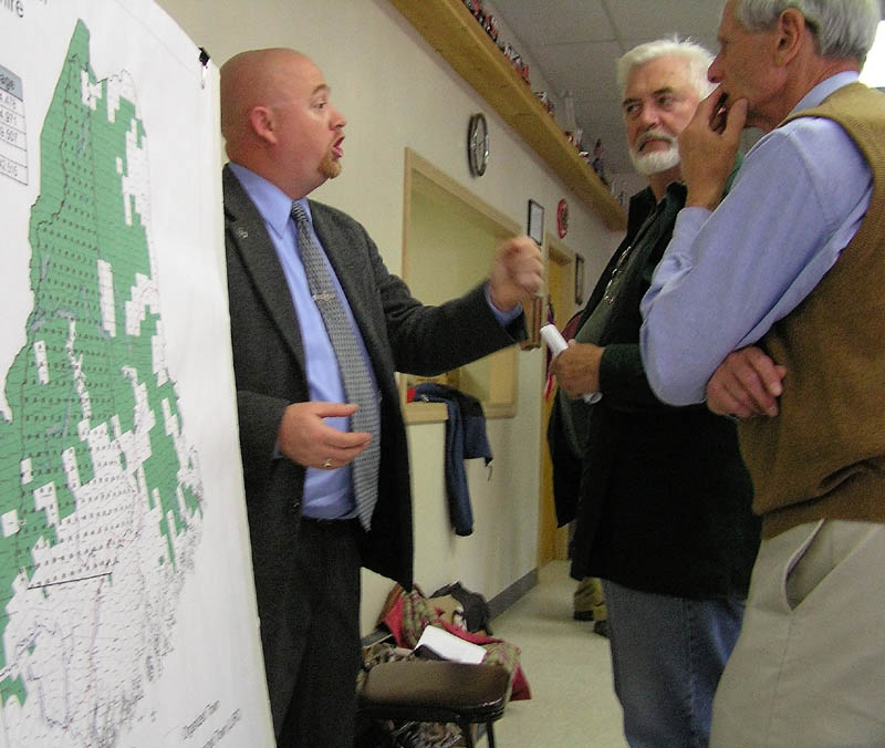 NEW RULES: Land Use and Regulatory Commission member Christopher Gardner, left, speaks with meeting attendees David Miller and Howard Trotzsky at the Solon Fire Station on Thursday.