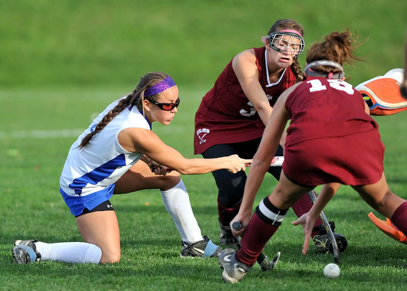 TAKE THE SHOT: Lawrence High School's Danielle Armour, left, takes a shot on goal between Edward Little High School defenders Kaelina Perron, center, and Kayla Nadeau in the second half of an Eastern A quarterfinal game Tuesday in Fairfield. Lawrence defeated Edward Little 2-0.