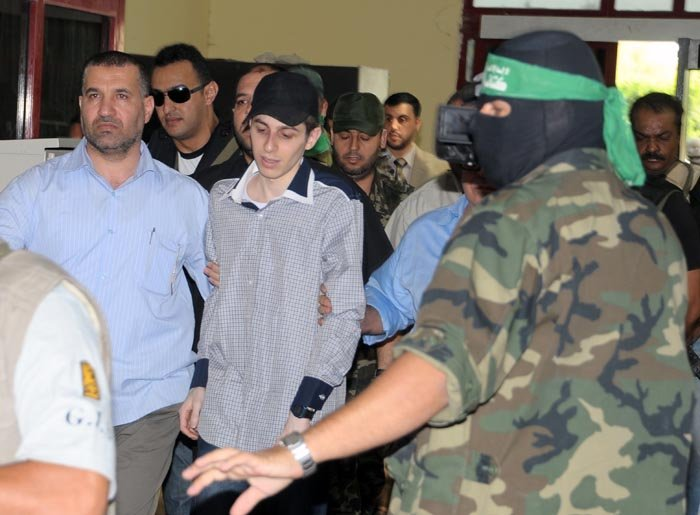 Looking dazed, thin and pale, Israeli soldier Gilad Schalit, center, is escorted by members of Hamas and the Egyptian mediators who helped arrange the tank crewman's release after more than five years in captivity.