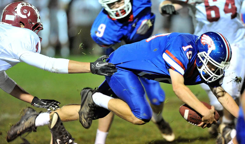 GOING FOR MORE: Messalonskee High School quarterback Travis St. Pierre dives for a first down in the first quarter against Bangor High School on Friday in Oakland.