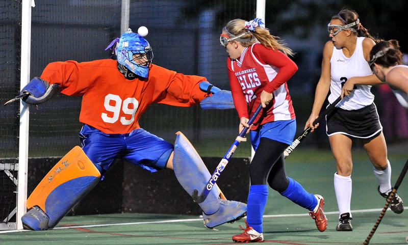 NOT GETTING IN: Messalonskee High School goalie Lexy Cole, left, blocks a shot with her head as teammate Bri Garland, center, helps defend Skowhegan's Makaela Michonski, right, in the first half of the Class A Kennebec Valley Athletic Conference championship game Wednesday at Colby College in Waterville.