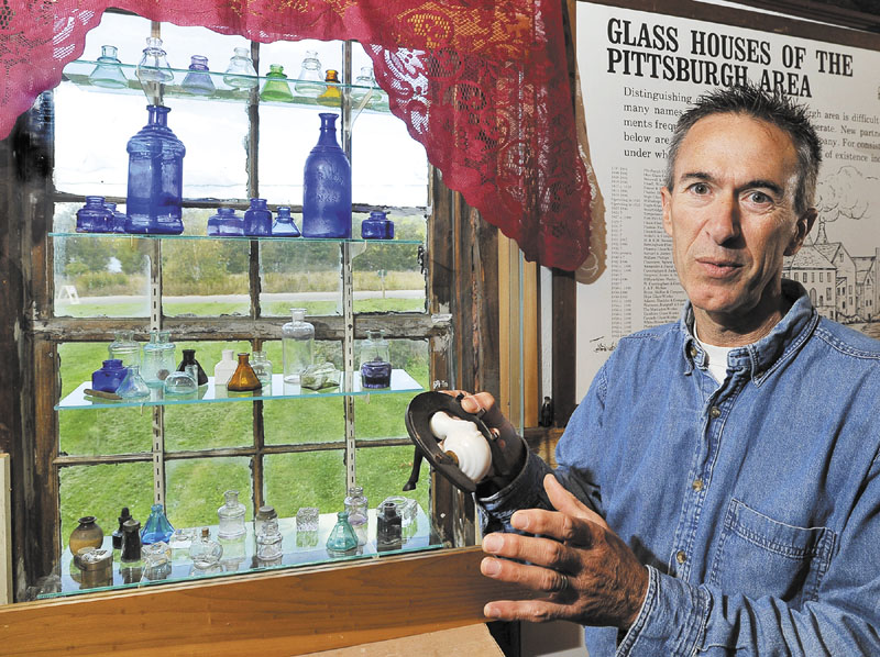 COLORFUL DISPLAY: Walter Bannon shows one of the more interesting glass objects — a milk glass snail shaped ink well that opens and closes to keep the ink fresh — Wednesday at his Maine Antique Bottle and Glass Museum in Bridgton.The bottle is attached to a real horseshoe with an attached horse leg to keep it stable during use, according to Bannon. In the window is a collection of glass ink bottles of various shapes and colors.