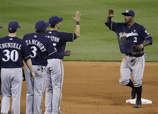 Milwaukee Brewers' Craig Counsell (30), Yuniesky Betancourt (3), Jerry Hairston Jr. and Nyjer Morgan (2) celebrate after Game 4 of baseball's National League championship series against the St. Louis Cardinals Thursday, Oct. 13, 2011, in St. Louis. The Brewers won 4-2. (AP Photo/Charles Rex Arbogast)
