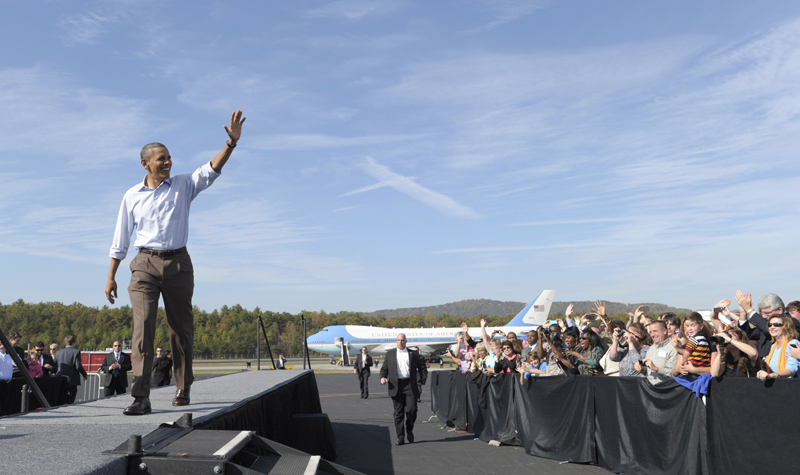 President Barack Obama greets people upon his arrival at Asheville Regional Airport in Fletcher, N.C., today at the beginning of a three-day bus tour promoting the American Jobs Act.