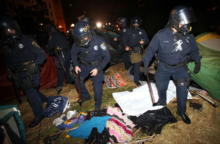 Oakland police search tents in Frank Ogawa Plaza as they disperse Occupy Oakland protesters today in Oakland, Calif. City officials had originally been supportive of the protesters, but the city later warned tthem that they were breaking the law and could not stay in the encampment overnight.