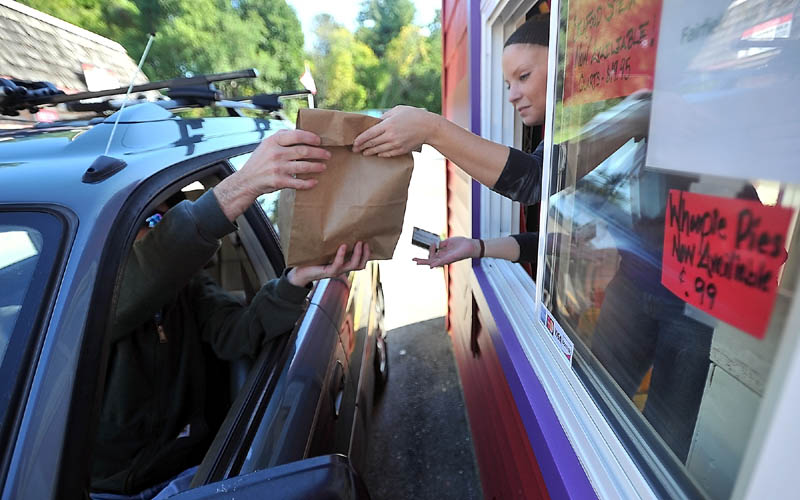 FAST FOOD: Danny McKinnis, left, picks up his order from Erin Falconer, right, at The Red Barn drive-through window Thursday afternoon in Winslow.
