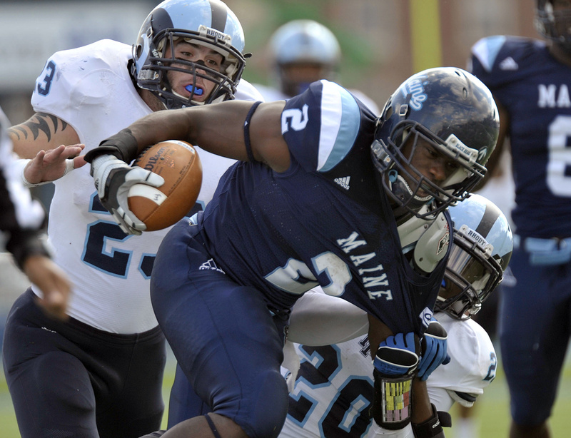 Maine running back Pushaun Brown is pulled down by Rhode Island's Michael Okunfolami, 20, and Doug Johnson in today's game at Orono. Brown ran for 103 yards and a TD in UMaine's 27-21 win.