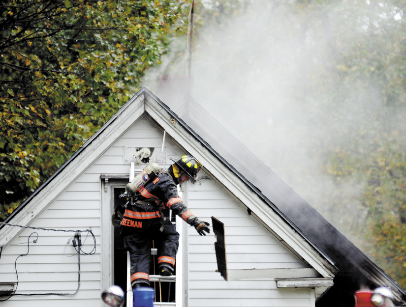 A firefighter removes a smoldering clapboard Sunday from a Richmond house that caught fire. A boy inside the home was hurt in the blaze, according to officials. The fire was reported around 10:30 a.m. and heavily damaged the home on River Road.