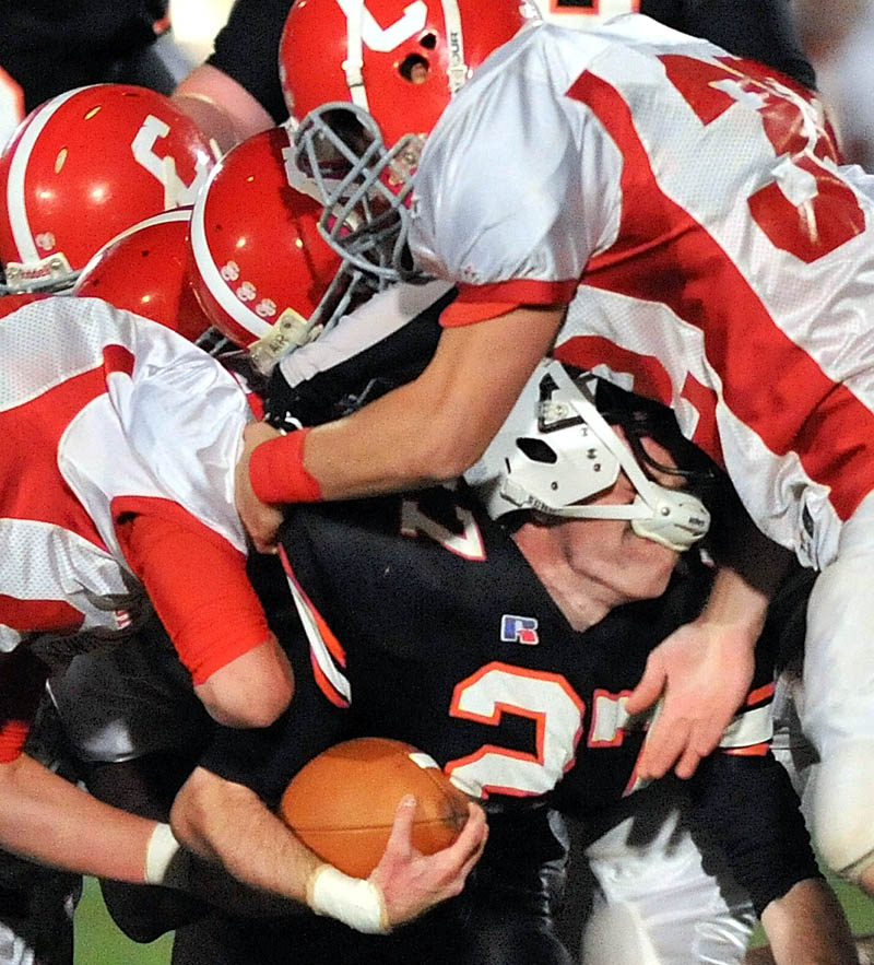 Skowhegan High School running back Adam Dusty, center, is tackled by Cony High School defenders during the second quarter Friday night in Skowhegan.