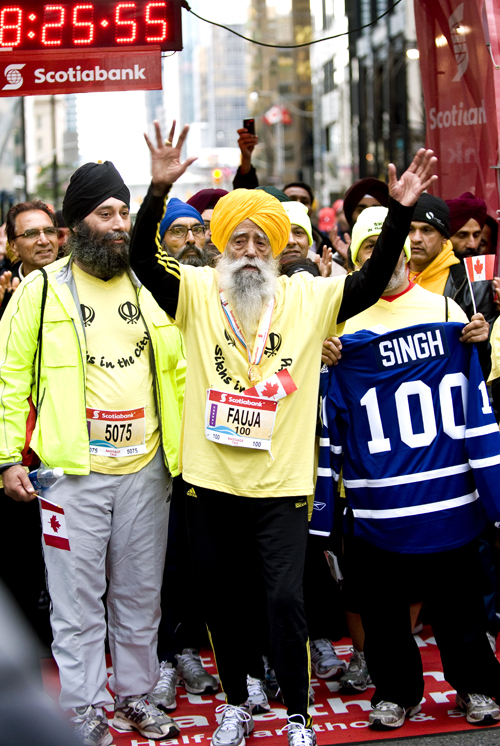 In this photo provided by Scotiabank Toronto Waterfront Marathon, Fauja Singh, 100, celebrates at the finish line after completing the Toronto Waterfront Marathon on Oct. 16.