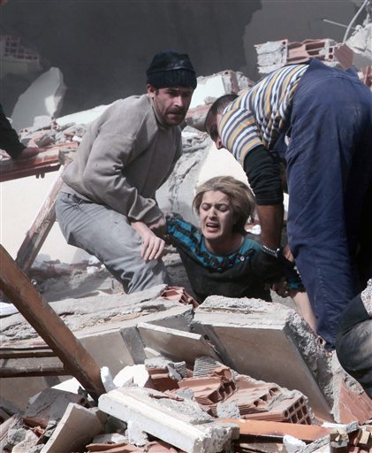 People rescue a woman trapped under debris after a powerful 7.2-magnitude earthquake struck eastern Turkey today, collapsing about 45 buildings in Van province.